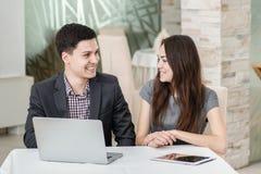 Удача! Молодые предприниматели сидя на таблице и смотреть стоковое изображение rf