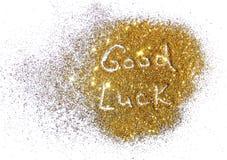 Удача надписи на золотой искре яркого блеска на белой предпосылке стоковое изображение