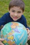 удерживание глобуса мальчика стоковое фото rf
