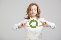 Удерживание женщины рециркулирует символ в его руках Стоковые Изображения RF