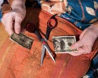 Удерживание женщины torned 100 долларовых банкнот Стоковая Фотография