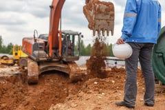 Удерживание и экскаватор рабочий-строителя стоковое изображение rf