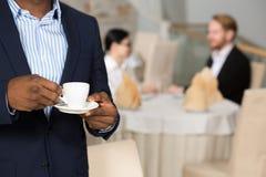 удерживание кофейной чашки бизнесмена Стоковая Фотография RF