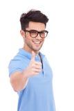 Удерживание молодого человека thumbs вверх Стоковые Изображения