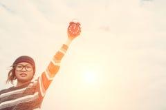 Удерживание молодой женщины и будильник хода к небу Стоковое Изображение RF