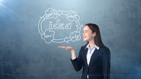 Удерживание молодой женщины покрасило экономический цикл на открытой ладони руки, над изолированной предпосылкой студии владение  Стоковое Изображение RF