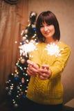 Удерживание молодой женщины сверкнает в ее руках около рождественской елки Стоковые Изображения
