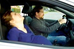 Удерживание человека катит внутри автомобиль вспугнутый о беременной женщине имея сужения стоковое фото rf