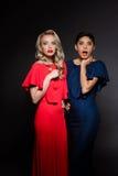 2 удивили красивых девушек в платьях вечера над серой предпосылкой Стоковое Изображение