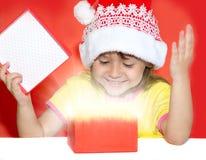 Удивленная девушка раскрывая подарок Стоковая Фотография