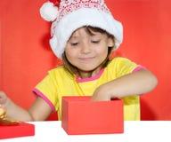 Удивленная девушка раскрывая подарок Стоковые Фото