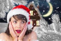 Удивленная женщина в шляпе santa против цифров произведенной предпосылки Стоковая Фотография