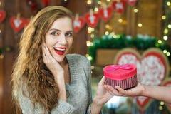 Удивленная женщина принимает подарок в коробке при сформированное сердце Стоковые Изображения