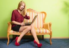 Удивленная женщина сидя на софе используя компьтер-книжку ПК Стоковые Фото