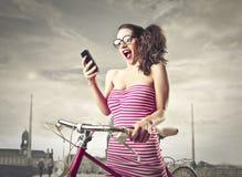 Удивленная женщина смотря ее телефон Стоковая Фотография