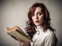 Удивленная женщина с книгой стоковые изображения