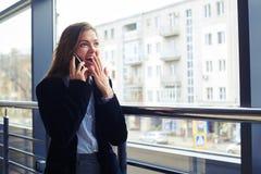 Удивленная женщина с рукой над раскрытым ртом во время convers телефона стоковая фотография