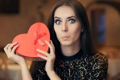 Удивленная красивая женщина держа подарок формы сердца Стоковая Фотография