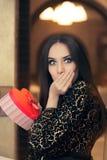Удивленная красивая женщина держа подарок формы сердца Стоковая Фотография RF