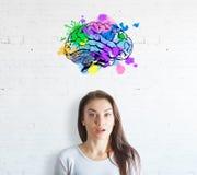 Удивленная молодая женщина на белой предпосылке кирпича с красочным эскизом мозга Стоковые Изображения