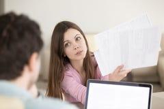 Удивленная молодая женщина показывая бумаги к человеку с спрашивая уборной Стоковое Фото