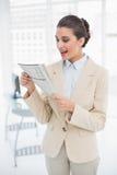 Удивленная умная коричневая с волосами коммерсантка читая газету Стоковое Изображение