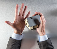 Удивленные агент недвижимости или продавец свойства держа дом Стоковое Изображение