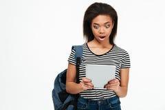 Удивленные афро американские новости чтения студента девушки от таблетки ПК Стоковые Фотографии RF