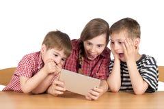 Удивленные братья и сестра при таблетка цифров изолированная на белизне Стоковое фото RF