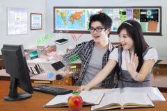 Удивленные студенты смотря экран компьютера Стоковые Фотографии RF