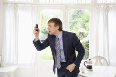 Удивленный бизнесмен смотря его сотовый телефон Стоковые Фото