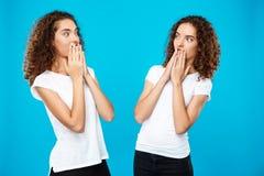 Удивленный 2 близнецам девушек смотря один другого над голубой предпосылкой Стоковое Изображение RF