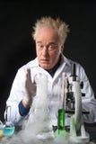 Удивленный врач-клиницист изучает в лаборатории и смотреть склянку Стоковые Изображения