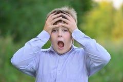 Удивленный мальчик держа его руки за головой Стоковая Фотография