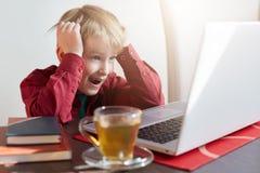 Удивленный мальчик liitle с светлыми волосами одел в красной рубашке сидя на таблице и наблюдая шаржах или блогах видео онлайн на Стоковая Фотография RF