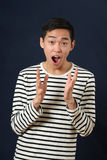 Удивленный молодой азиатский человек показывать с 2 руками Стоковая Фотография RF