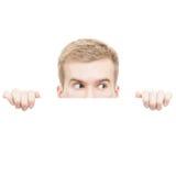 Удивленный молодой человек смотря от за доски изолированной на белой предпосылке Стоковые Изображения RF
