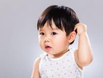 Удивленный младенец царапая голову стоковое фото rf
