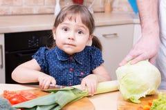 Удивленный лук вырезывания девушки ребенка с dan на кухне Стоковые Фото