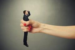 Удивленный человек зажатый в большом женском кулаке Стоковая Фотография