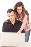 Удивленный человек и женщина смотря компьтер-книжку Стоковая Фотография RF