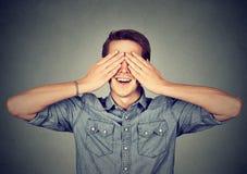 Удивленный человек покрывая его наблюдает усмехаться стоковая фотография