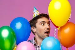 Удивленный человек празднуя день рождения, держа красочные baloons над фиолетовой предпосылкой Стоковое Фото