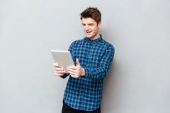 Удивленный человек смотря планшет стоковая фотография