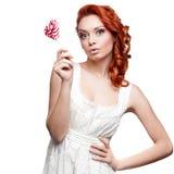 Удивленный red-haired lollipop удерживания женщины стоковое фото