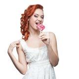 Удивленный red-haired lollipop удерживания женщины стоковые фотографии rf