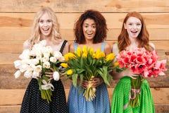 3 удивленных женщины держа букеты цветков Стоковые Изображения RF