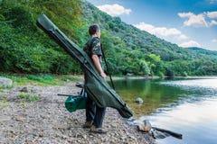 Удить приключения, рыбная ловля карпа Рыболов на береге озера с рыболовными принадлежностями камуфлирования Стоковая Фотография