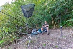 Удить приключения, рыбная ловля карпа Рыболов на береге озера Стоковые Изображения RF