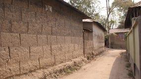 Улица деревни показывая дома грязи и дорогу рухляка Стоковое Фото